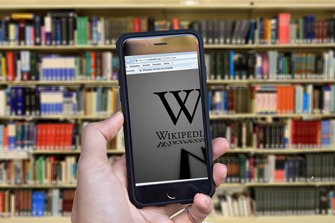 mobile with wikipedia against library backdrop